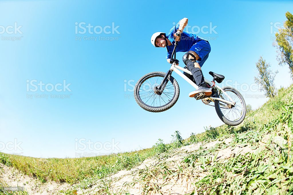 cyclist riding jumping with bicycle cross-country stock photo