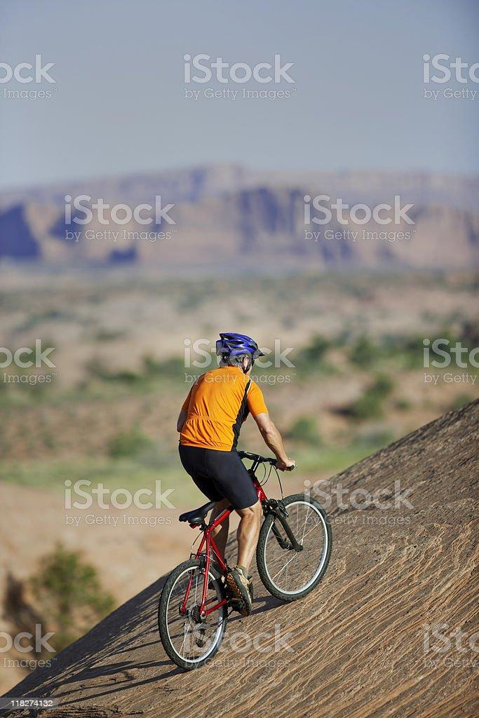 Cyclist Riding Mountain Bike Uphill On Slickrock Trail royalty-free stock photo