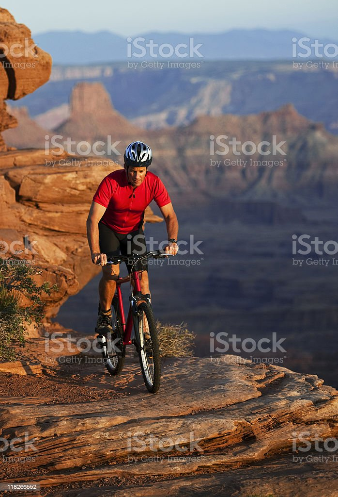 Cyclist Riding Mountainbike On Edge Of Huge Canyon In Utah stock photo