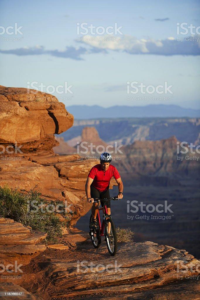 Cyclist Riding Near Edge of Rocky Ledge In Moab, Utah stock photo