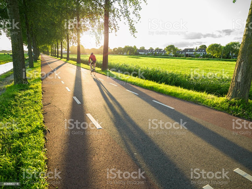 Cyclist Riding On The Country Road In Sunset stock photo