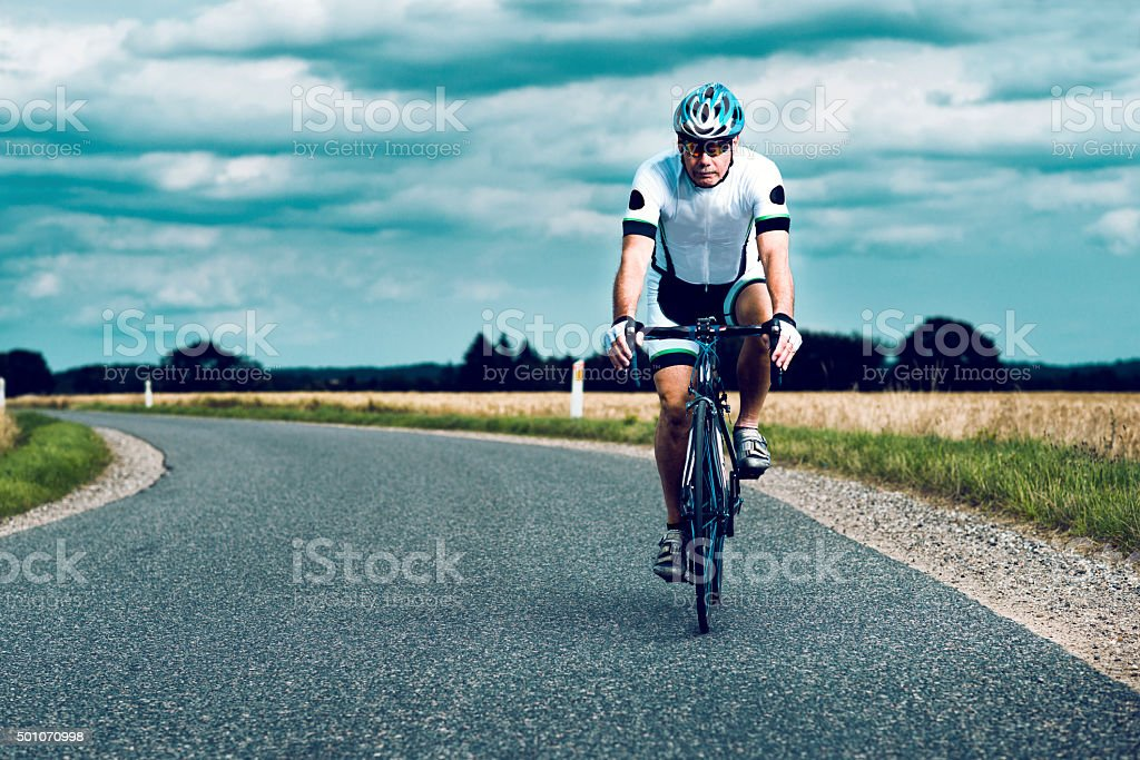 Cyclist wears helmet and rides bike on a rural road stock photo