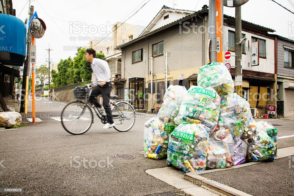 Cyclist zooms past pile of recyclable garbage in Kyoto street stock photo