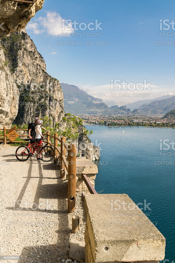 Cyclists admire the panorama from the Ponale trail. stock photo
