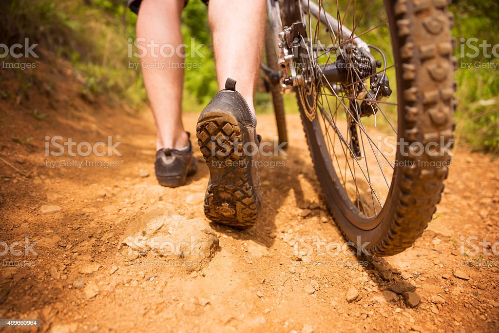Cyclist's feet and a bike tire on a dolomite road stock photo