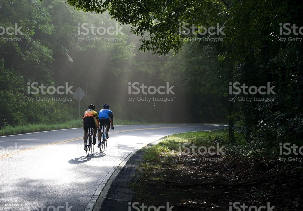 Cyclists on country side road stock photo