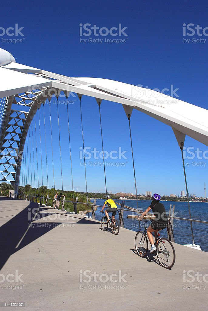 Cyclists on geometric bridge stock photo