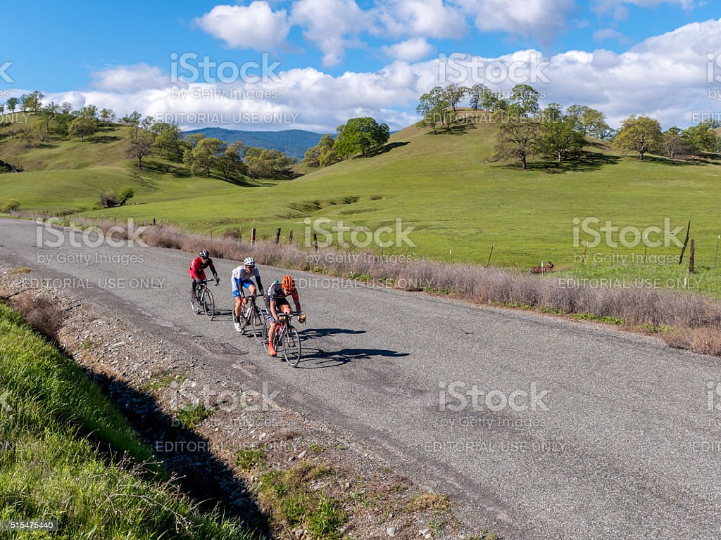 Cyclists road racing in spring foothills stock photo