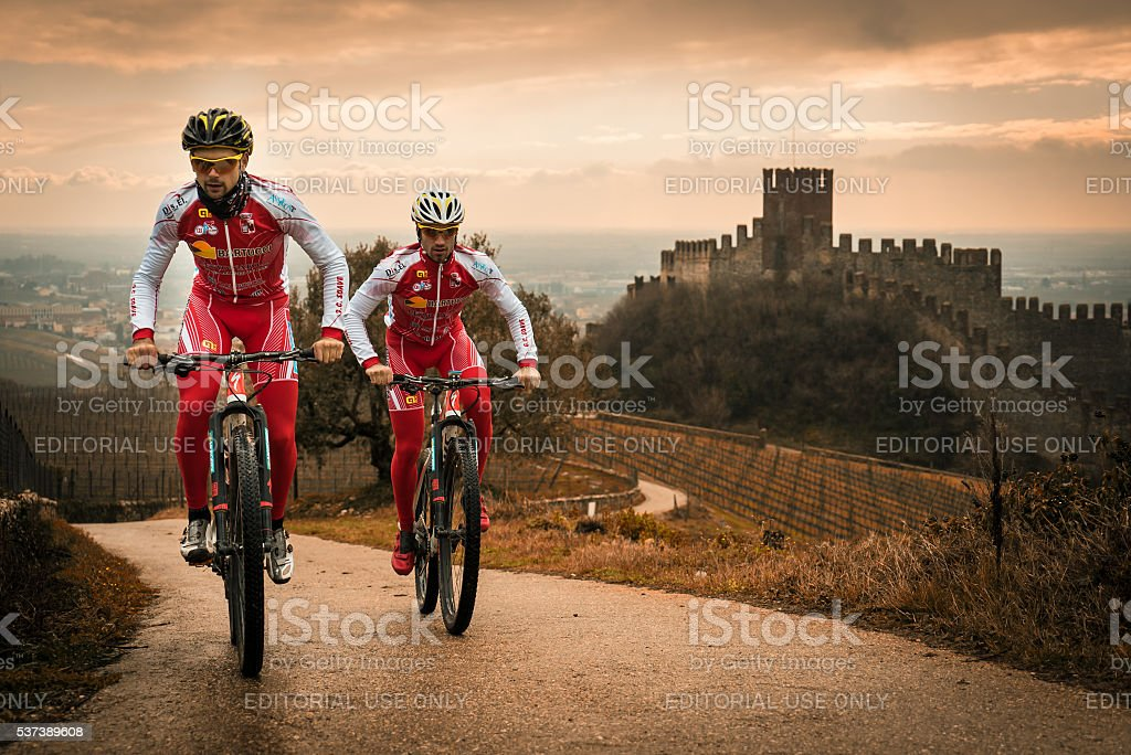 Cyclists train on the hills surrounding the castle of Soave. stock photo