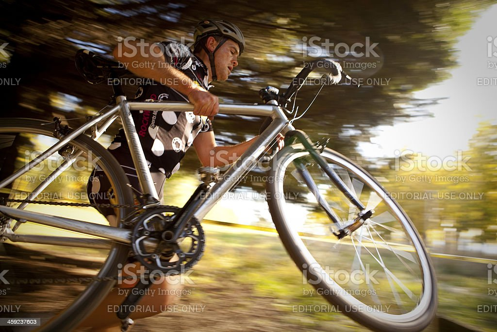 Cyclocross racer carrying his bike over obstacles stock photo