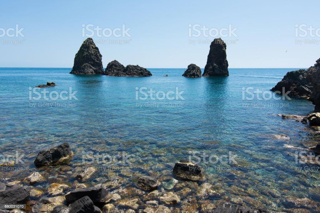 Cyclops islands, Acitrezza, Sicily. Basalt rocks on the sea stock photo