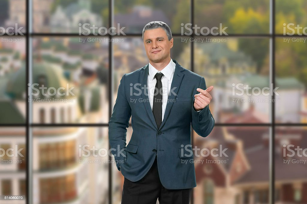 Cynical adult businessman at workplace. stock photo