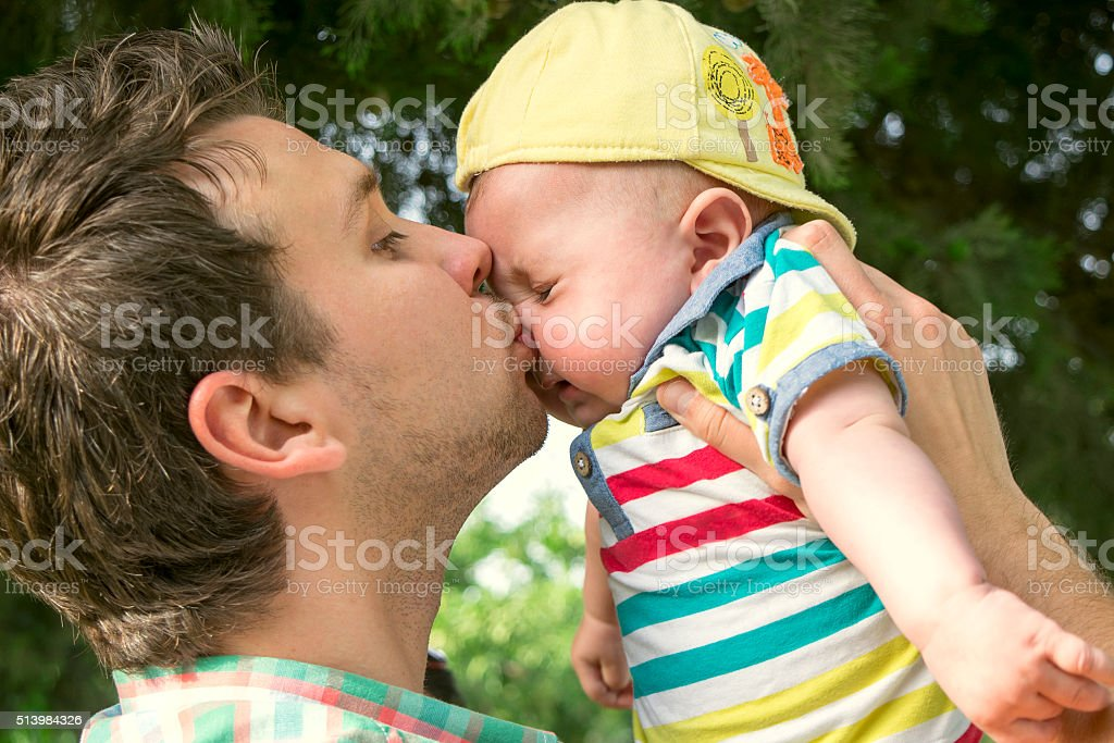 dad and baby son outdoors stock photo