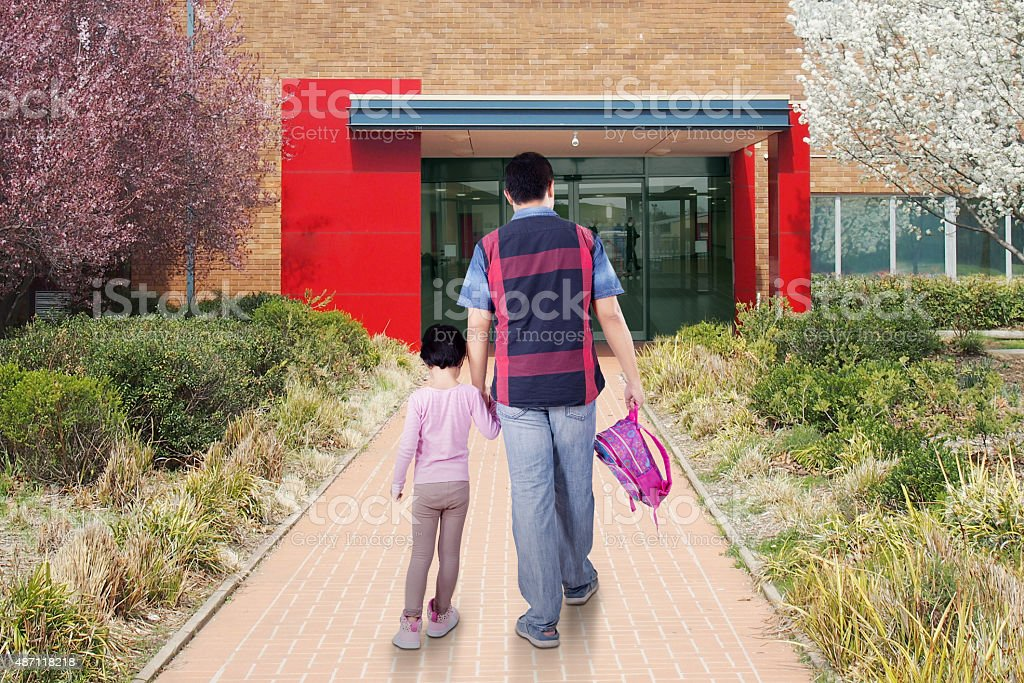 Dad and child arrive at school stock photo