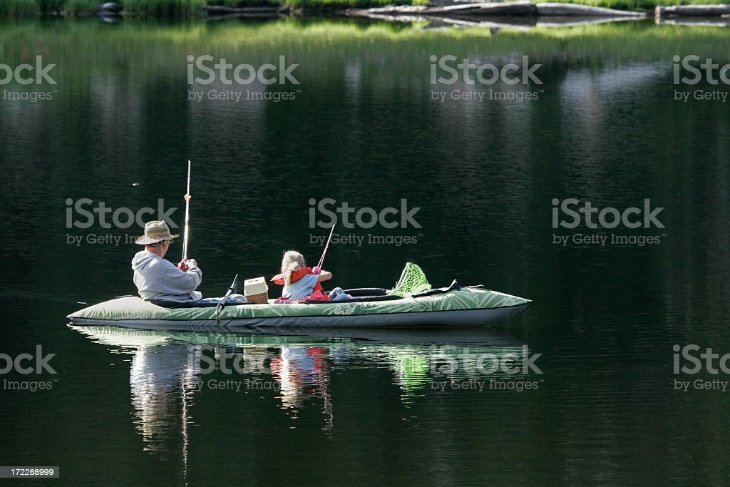 Dad and daughter fishing in a canoe royalty-free stock photo