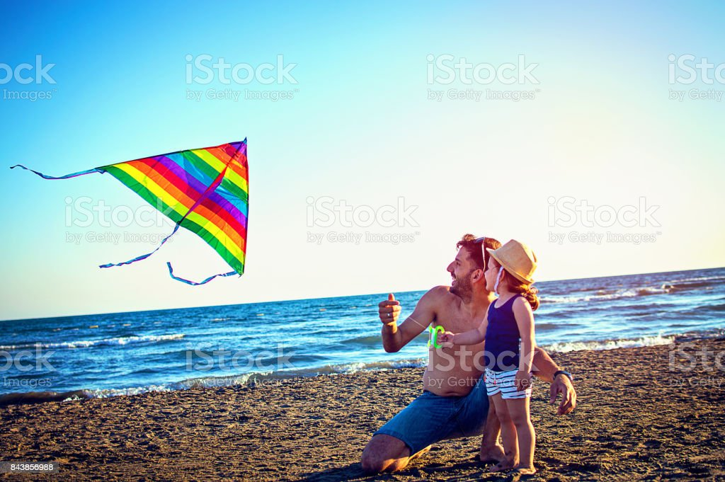 Dad and daughter flying kite together at tropical sunny beach stock photo