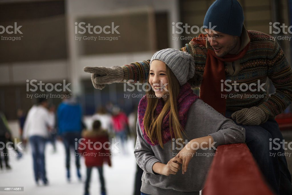Dad and daughter ice skating,indoor stock photo