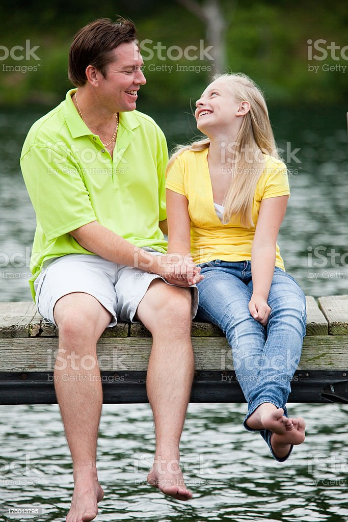 Dad and Daughter Laughing on a dock royalty-free stock photo
