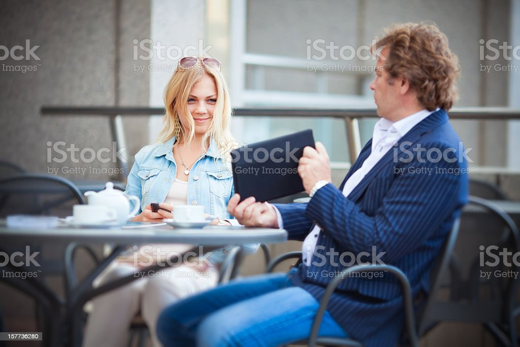 Dad and Daughter Using Digital Tablet Outdoor in Cafe royalty-free stock photo