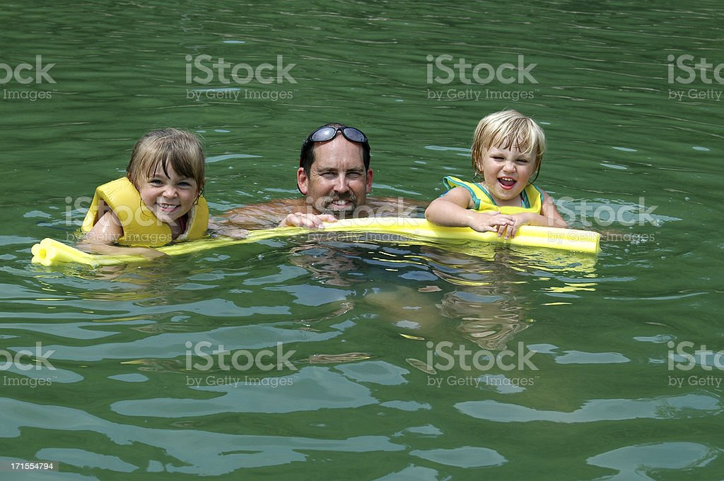 Dad and his girls swimming stock photo