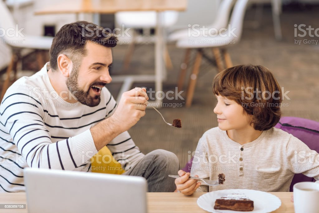 Dad and little boy eating chocolate cake stock photo