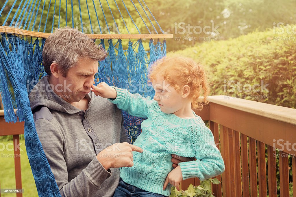 Dad and little redhead girl arguing in a hammock. royalty-free stock photo