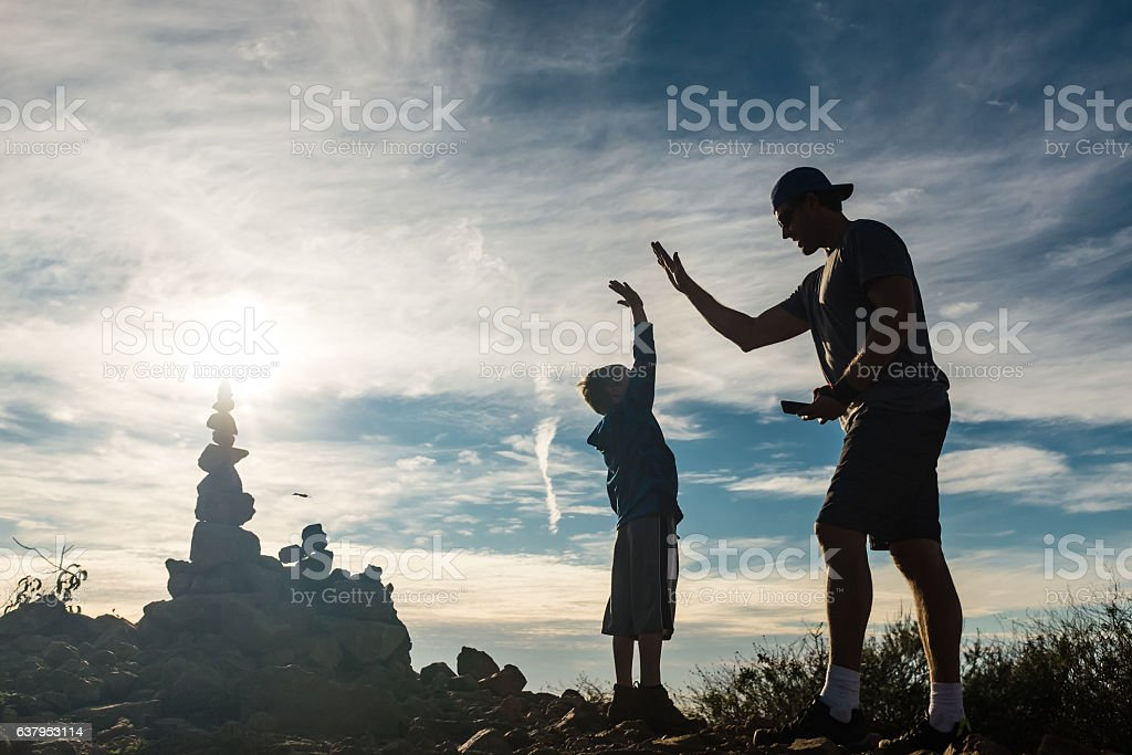 Dad And Son At Top Of Their Hike Celebrating stock photo