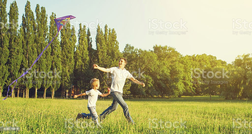 Dad and son child flying a kite in summer nature stock photo