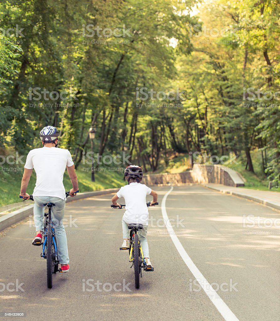 Dad and son cycling stock photo