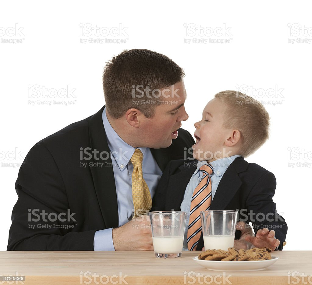 Dad and son enjoying milk with cookies royalty-free stock photo