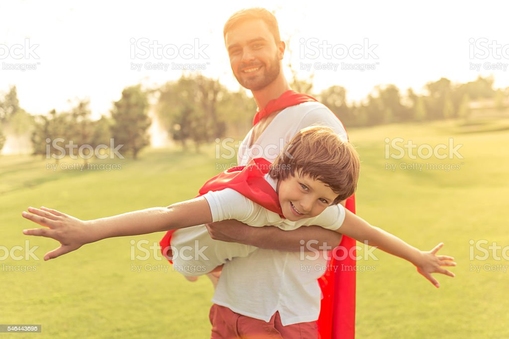 Dad and son playing superheroes stock photo