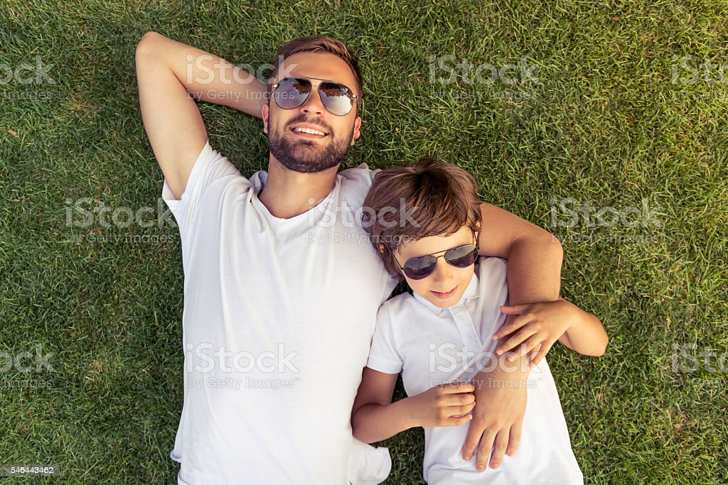 Dad and son resting outdoors stock photo