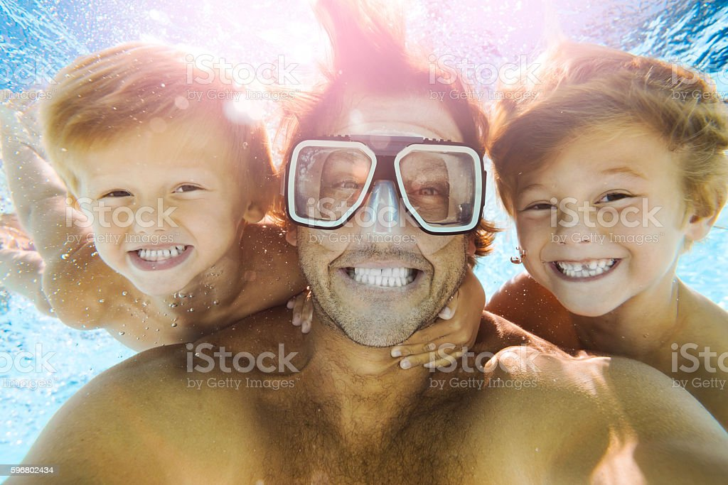Dad and Sons Having Fun Doing A Selfie Underwater stock photo