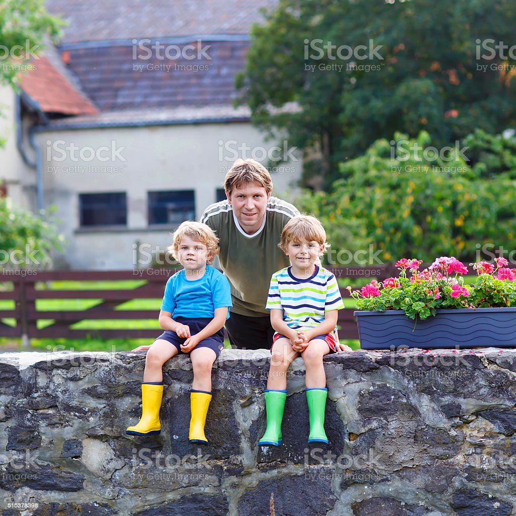 dad and two little kid boys sitting together on  bridge stock photo