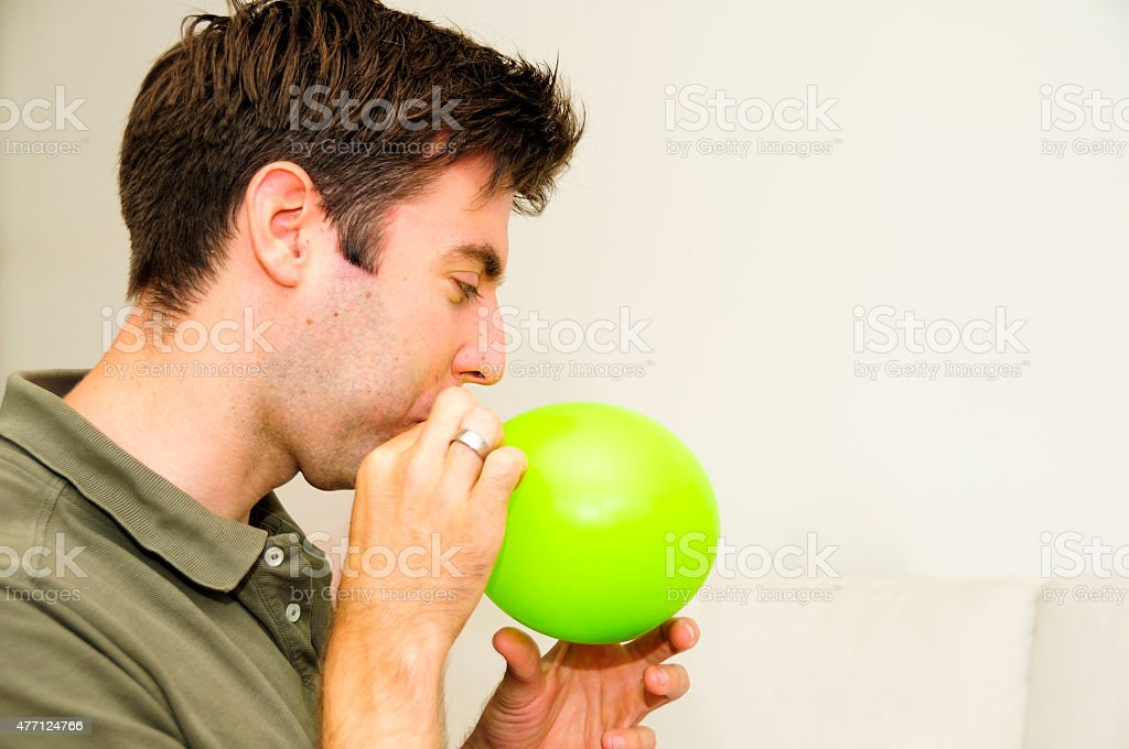 Dad blowing green ballon inflating close-up indoors casual stock photo