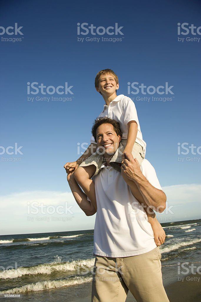 Dad carrying son on his shoulders. royalty-free stock photo