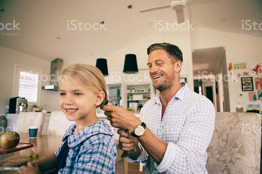 dad combing daughter's hair for school stock photo