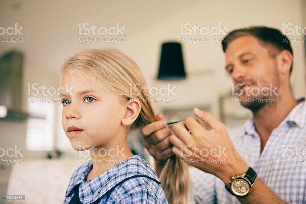 dad combing daughters hair in the morning stock photo