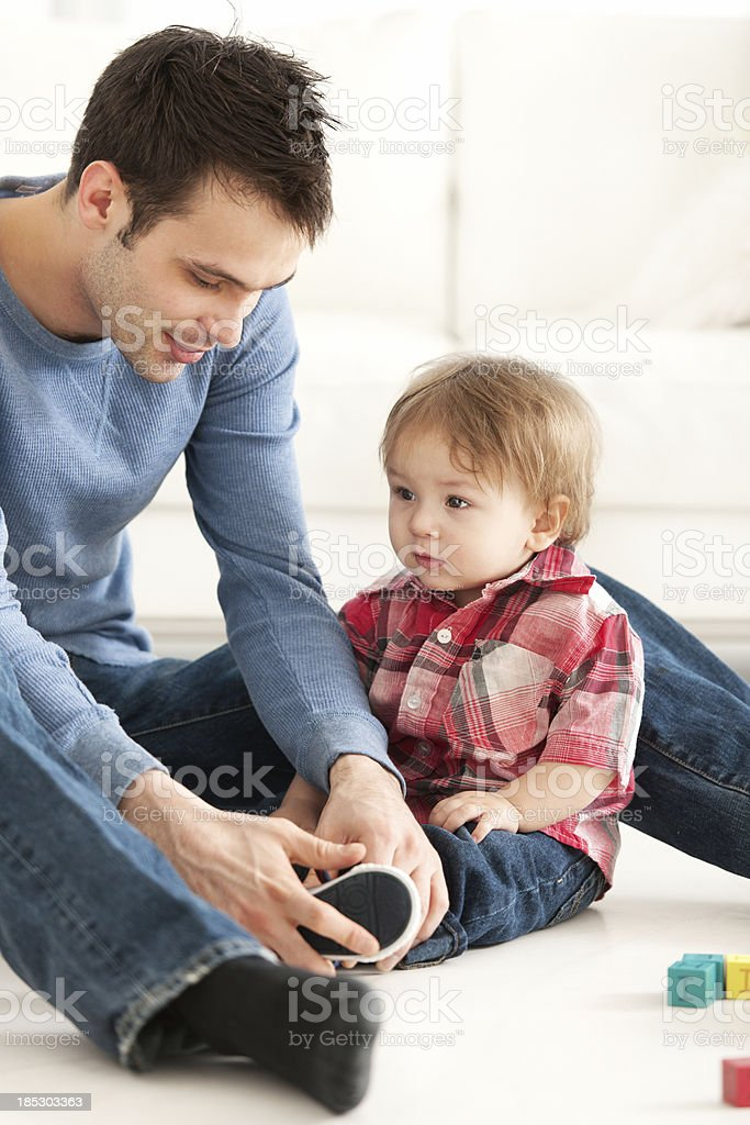 Dad dressing his son royalty-free stock photo