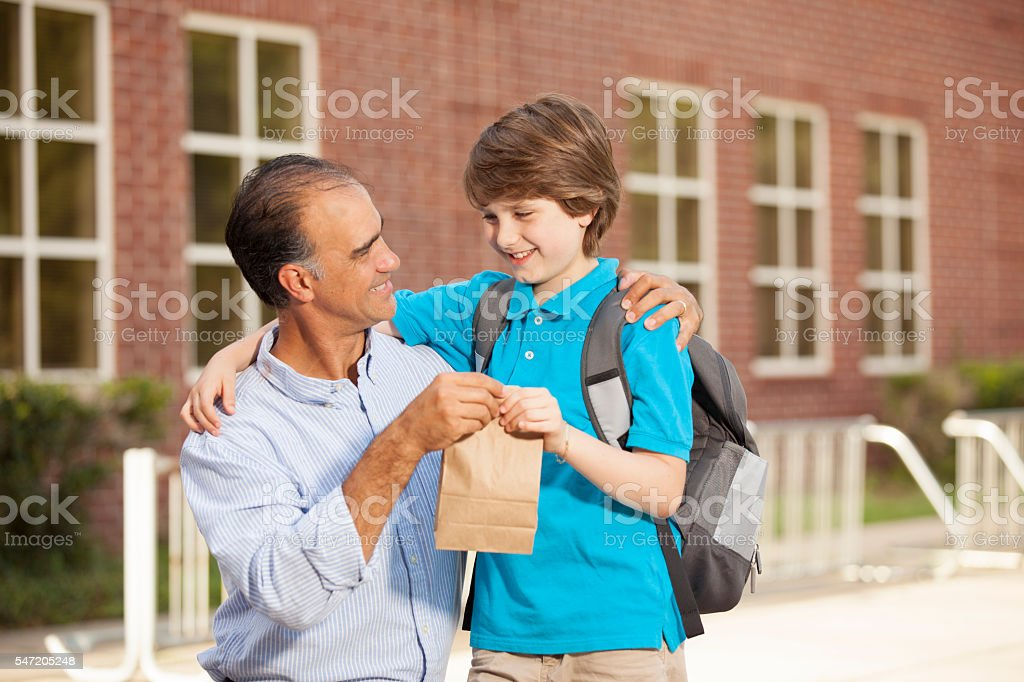 Dad gives lunch sack to boy.  First day of school. stock photo
