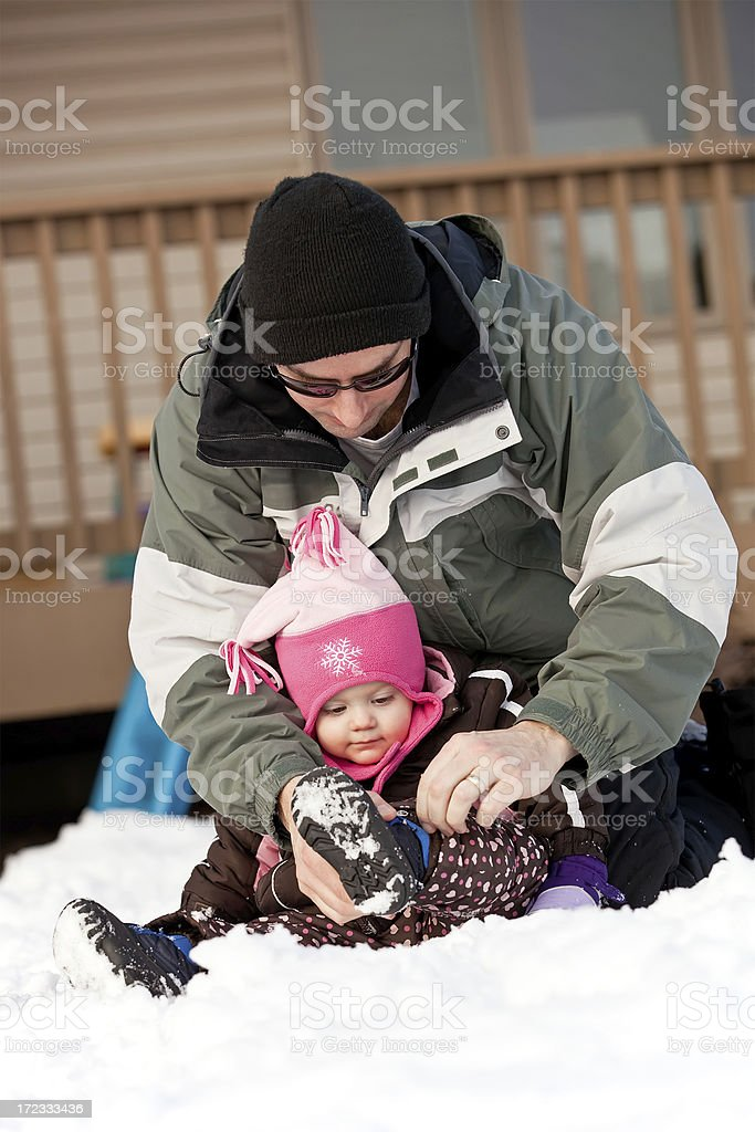 Dad Helping Girl With Snow Boot royalty-free stock photo
