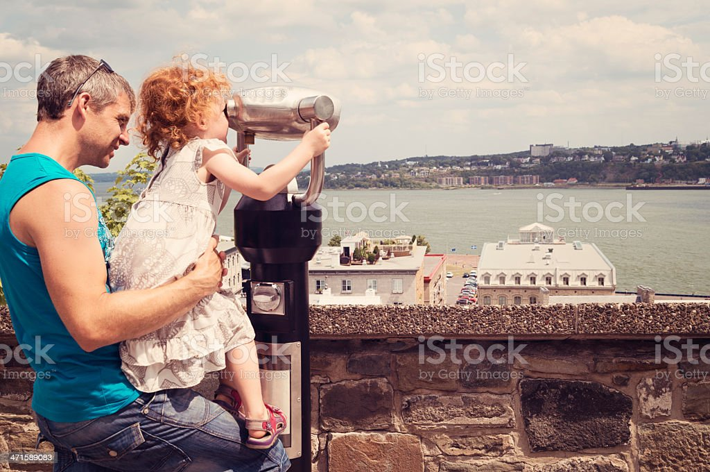 Dad helping little girl to sightsee the city of Quebec. stock photo