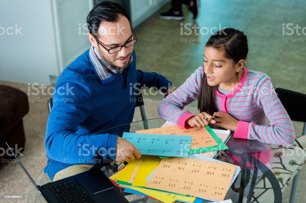 Dad helps daughter with math homework stock photo