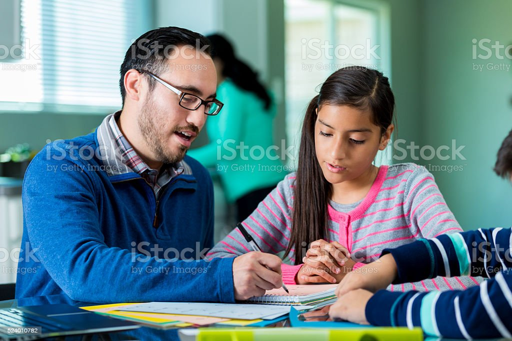 Dad helps his kids with homework assignments stock photo