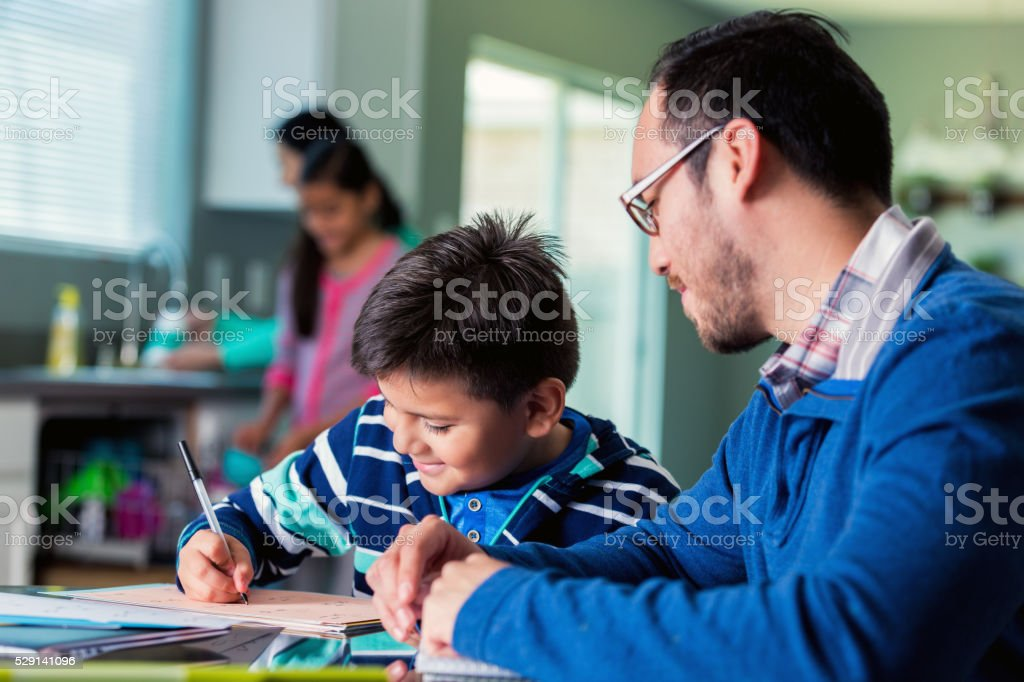 Dad helps son with homework assignment stock photo