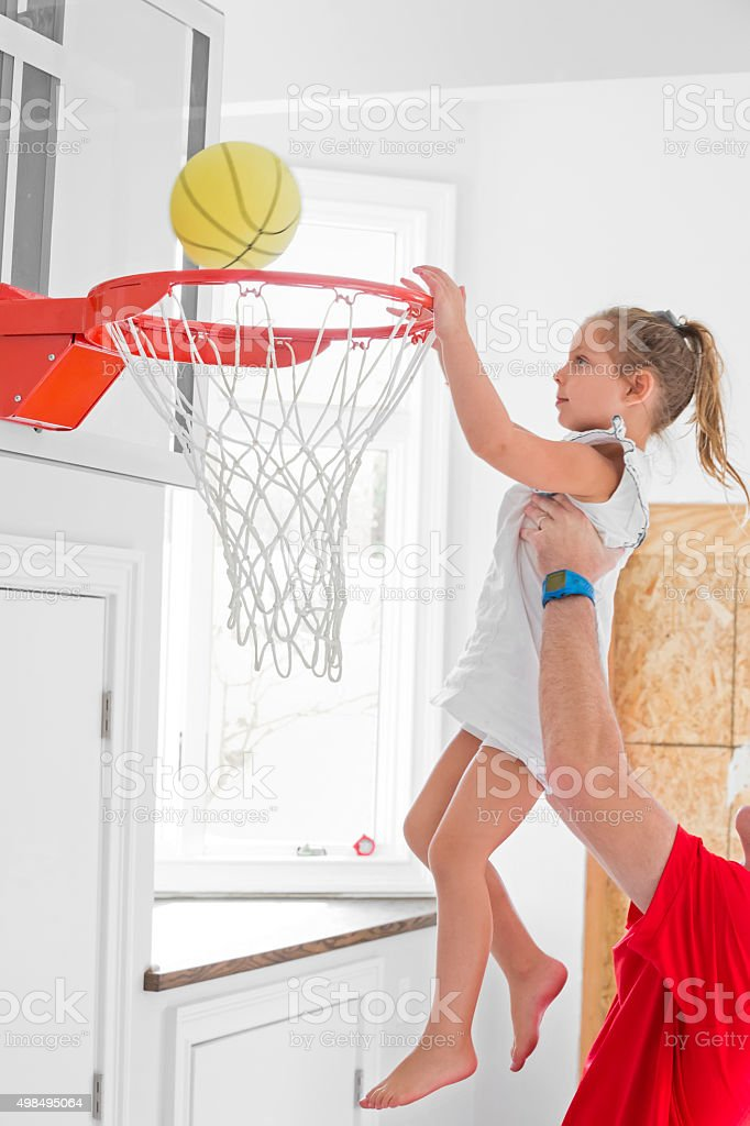 Dad holds young daughter as she puts basketball in net stock photo