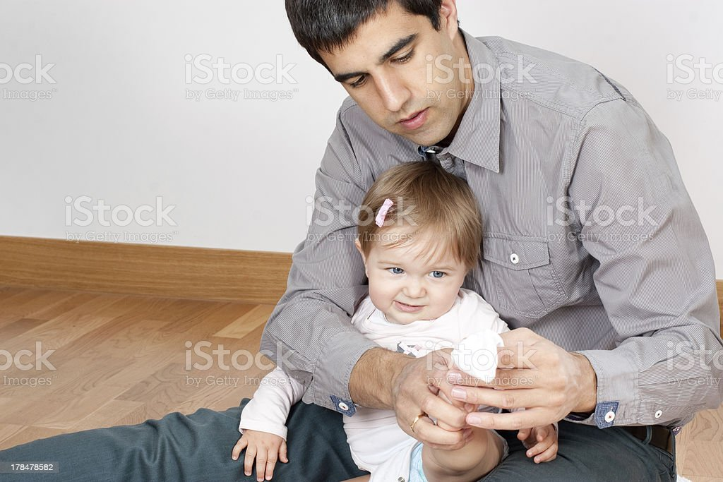 Dad is not very skillful dressing up babys royalty-free stock photo