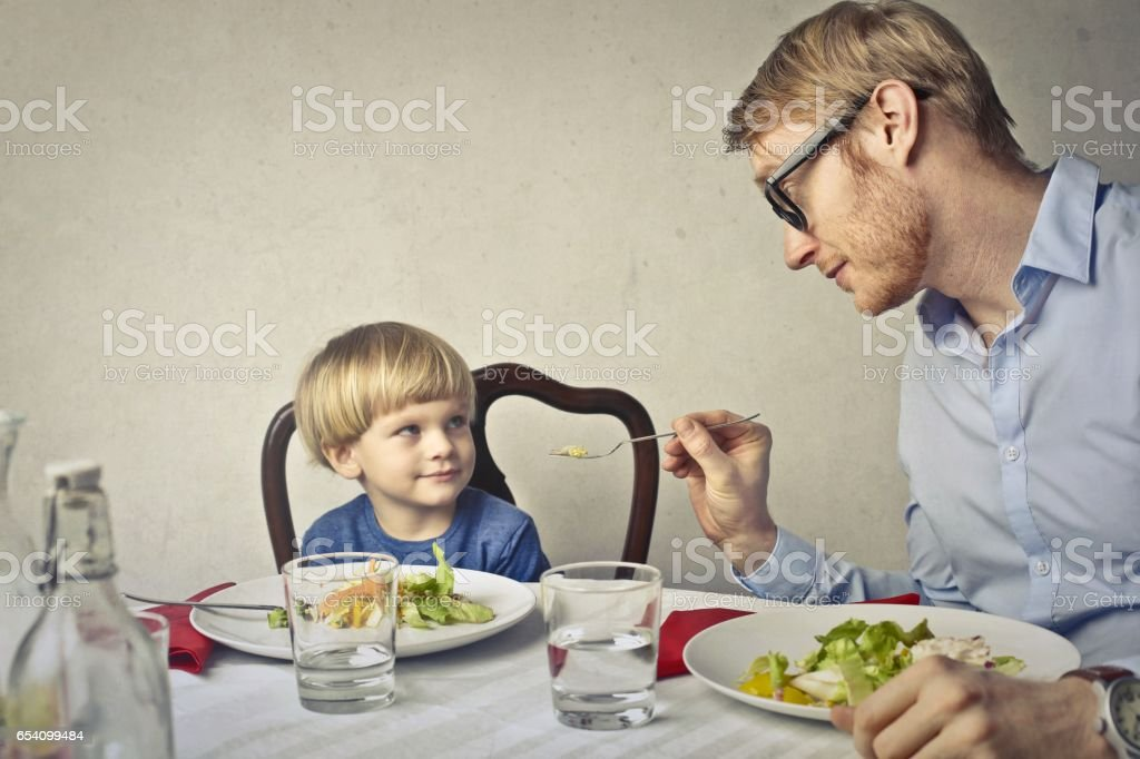 Dad is trying to make his son eat stock photo