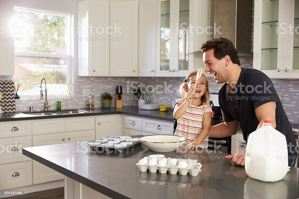 Dad laughs as girl puts cake mix on his nose in the stock photo