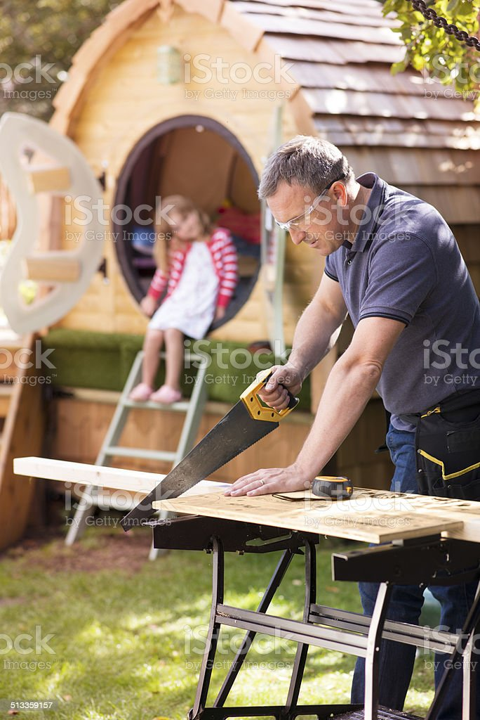 dad makes a treehouse stock photo